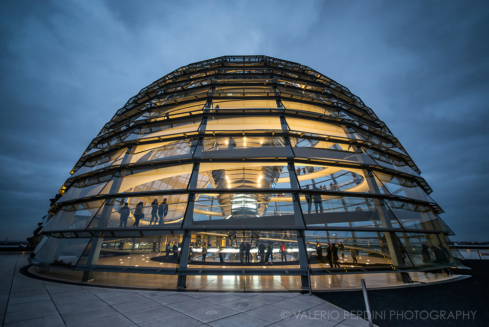 The current Reichstag dome is a glass dome, constructed on top of the rebuilt Reichstag building in Berlin. It was designed by architect Norman Foster and built to symbolize the reunification of Germany. The distinctive appearance of the dome has made it a prominent landmark in Berlin. The Reichstag dome is a large glass dome with a 360 degree view of the surrounding Berlin cityscape. The debating chamber of the Bundestag, the German parliament, can be seen down below. A mirrored cone in the center of the dome directs sunlight into the building, and so that visitors can see the working of the chamber. The dome is open to the public and can be reached by climbing two steel, spiraling ramps that are reminiscent of a double-helix. The Dome symbolizes that the people are above the government, as was not the case during National Socialism. [Wiki]