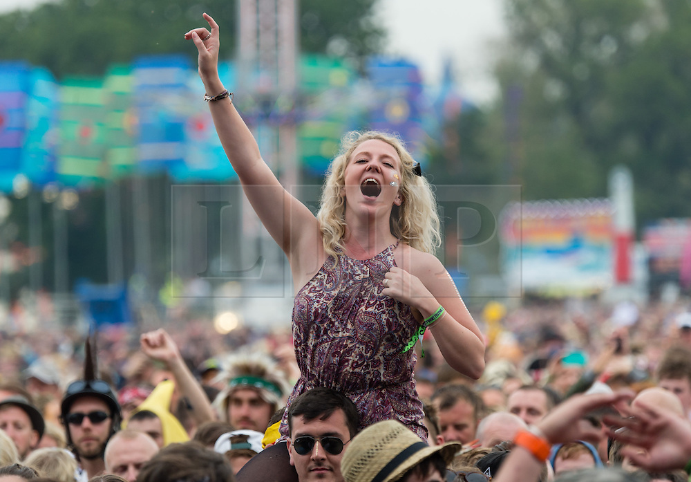 © Licensed to London News Pictures. 12/06/2015. Isle of Wight, UK.  Festival goers on their friends shoulders dance and listen to music in the pouring rain, as Kodaline perform on the main stage at Isle of Wight Festival 2015 on Friday Day 2.  Yesterday the weather was hot and Sunny.  This afternoon has seen torrential rain downpoors.  This years festival include headline artists the Prodigy, Blur and Fleetwood Mac.  Photo credit : Richard Isaac/LNP