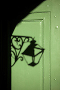 Shadow of a gas lamp on a green door in the French Quarter of New Orleans, Louisiana.