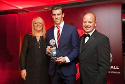 CARDIFF, WALES - Monday, October 6, 2014: Wales' Gareth Bale is presented with the Fans' Player of the Year Award by Chief-Executive Jonathan Ford and Vauxhall's Cheryl Stibbs at the FAW Footballer of the Year Awards 2014 held at the St. David's Hotel. (Pic by David Rawcliffe/Propaganda)