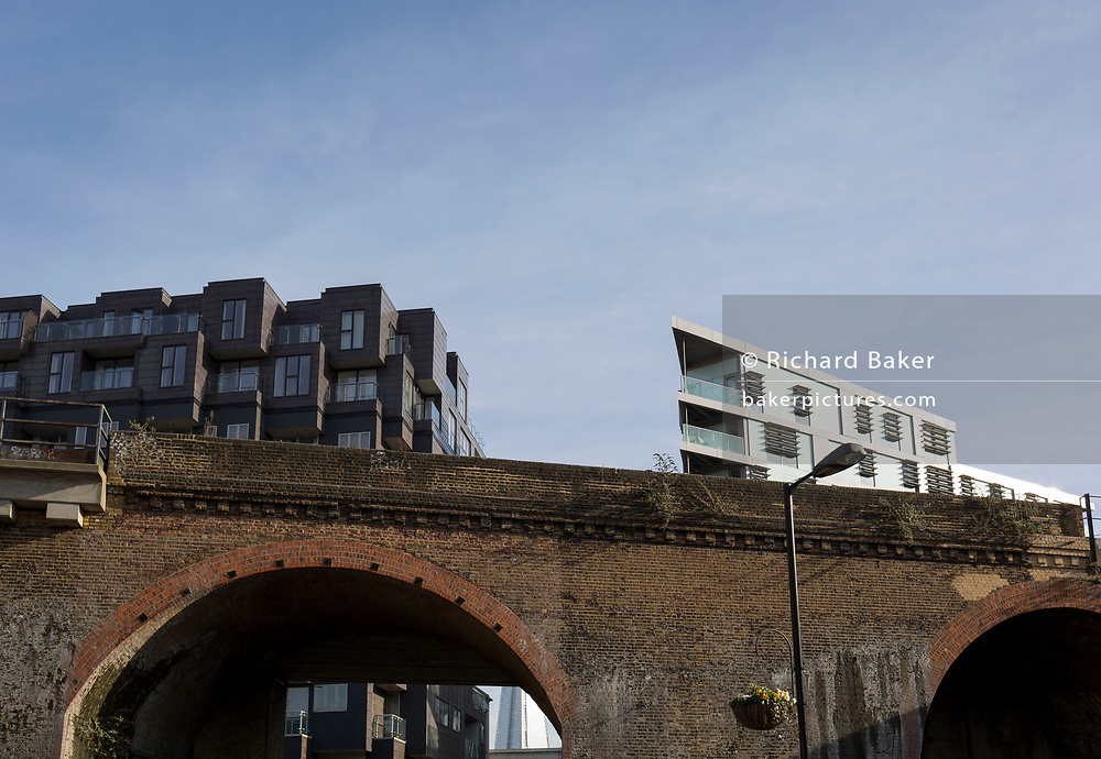 Old Victorian railway bridge and new housing in the borough of Southwark, on 30th January 2018, in London, England.
