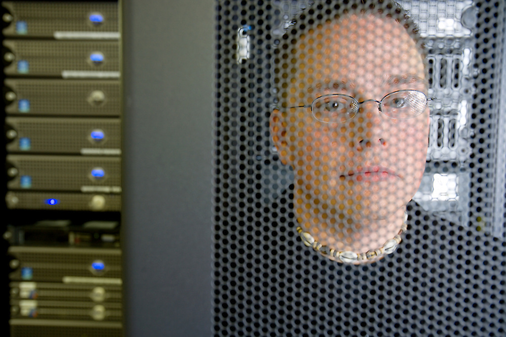 Portrait of Lance Fischer, network systems manager Balls Food Stores, among the computer servers.