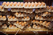 Trays of eggs stacked precarious at a farmers market