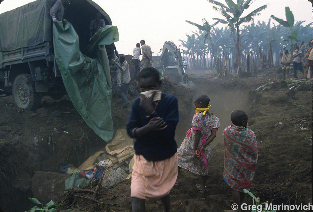 Goma, Zaire, Rwandan refugee children watch the bodies of a cholera epidemic being dumped in mass graves outside Goma, eastern Zaire. Millions of ethnic Hutus escaped the RPF takeover that followed and stopped the genocide of Rwandan Tutsis and Hutu moderates by extremist Hutus. 1994. Greg Marinovich