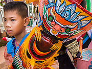 28 JUNE 2014 - DAN SAI, LOEI, THAILAND: A boy waits for the ghost festival parade to start in Dan Sai. Phi Ta Khon (also spelled Pee Ta Khon) is the Ghost Festival. Over three days, the town's residents invite protection from Phra U-pakut, the spirit that lives in the Mun River, which runs through Dan Sai. People in the town and surrounding villages wear costumes made of patchwork and ornate masks and are thought be ghosts who were awoken from the dead when Vessantra Jataka (one of the Buddhas) came out of the forest.    PHOTO BY JACK KURTZ