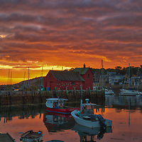 New England photography of Motif #1, a famous red fishing shack in Rockport, Massachusetts on Cape Ann. The photo captures the local fishing boats with the iconic landmark and a stunningly beautiful sunrise sky. The historic landmark is known throughout New England as Motif #1, so called because it is the most often painted building in America.<br />