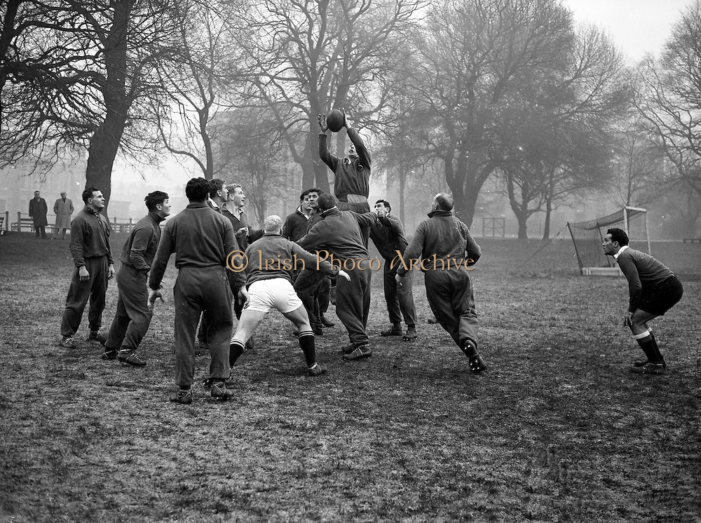 A Malan, captain of the South African team going for a high ball in their early practice at College Park Dublin,..Irish Rugby Football Union, Ireland v South Africa, Tour Match, South African team practice, College Park, Dublin, Ireland, Thursday 15th December, 1960,.15.12.1960, 12.15.1960,..South African Team, ..L G Wilson, Wearing number 15 South African jersey, Full Back, Western Province Rugby Football Club, Cape Town, South Africa, ..AN Other, Wearing number 13 South African jersey, Left Wing, ..A I Kirkpatrick, Wearing number 12 South African jersey, Left Centre, Orange Free State Rugby Football Club, Bloemfontein, South Africa, ..J L Gainsford, Wearing number 11 South African jersey, Right Centre, Western Province Rugby Football Club, Cape Town, South Africa, ..J P Engelbrecht, Wearing number 14 South African jersey, Right Wing, Western Province Rugby Football Club, Cape Town, South Africa,..K Oxlee, Wearing number 10 South African jersey, Stand Off, Natal Rugby Football Club, Durban, South Africa,..R J Lockyear, Wearing number 9 South African jersey, Scrum Half, Griqualand West Rugby Football Club, Kimberley, South Africa, ..S P Kuhn, Wearing number 1 South African jersey, Loose Head Prop, Transvaal Rugby Football Club,  Johannesburg, South Africa,..R A Hill, Wearing number 2 South African jersey, Hooker, Rhodesia Rugby Football Club, Rhodesia, Zimbabwe,..P S du Toit, Wearing number 3 South African jersey, Tight Head Prop, Boland Rugby Football Club, Wellington, South Africa, ..A S Malan, Wearing number 4 South African jersey, Captain of the South African team, Lock, Transvaal Rugby Football Club,  Johannesburg, South Africa,..J T Claassen, Wearing number 5 South African jersey, Lock, West Transvaal Rugby Football Club,  Johannesburg, South Africa,..G H Van ZYL, Wearing number 6 South African jersey, Flank, Western Province Rugby Football Club, Cape Town, South Africa, ..H J M Pelser, Wearing number 7 South African jersey, Number 8, Transvaal Rugby Football
