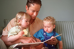 Father sitting on sofa reading story book with young son and daughter,