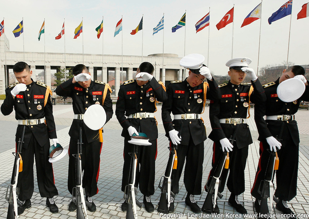 Guards of honor from the South Korean marine corps wipe sweat after a performance at the War Memorial of Korea in Seoul April 3, 2009. /Lee Jae-Won