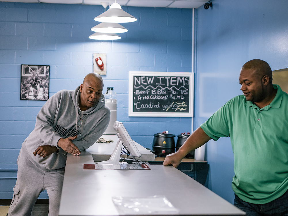 Michael Graham talks with business partner Terry Thomas, right, as they prepare to open Michael G's Breakfast & BBQ at two locations in Maryland.
