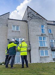 © Licensed to London News Pictures. 13/02/2014. Aberystwyth, UK Police and CANTREF Housing Association officers are evacuating tenants and owners of flats in the PLAS MOROLWG complex overlooking Aberystwyth harbour after large parts of the roofs and facias of the buildings were torn off at the height of the ferocious winds yesterday.. Photo credit : Keith Morris/LNP
