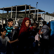 Moria camp refugees walk past the aftermath of a fatal fire that claimed the life of a woman and a child the night before. Clashes between refugees and police resulted after the blaze, where 12,000 refugees and migrants remain trapped in squalid living conditions on Lesvos Island in Greece on Sunday, September 29, 2019.