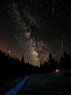 A stargazer finds warmth by a campfire as the Perseid Meteor Shower rains down from above.