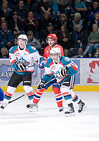 KELOWNA, CANADA, JANUARY 4: Cole Martin #8 and Shane McColgan #18 of the Kelowna Rockets check Liam Stewart #11 of the Spokane Chiefs as the Spokane Chiefs visit the Kelowna Rockets on January 4, 2012 at Prospera Place in Kelowna, British Columbia, Canada (Photo by Marissa Baecker/Getty Images) *** Local Caption ***