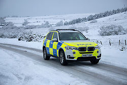 © Licensed to London News Pictures Ltd.. 01/02/2019. Bodmin Moor, UK. A police car drives along the  A30 on Bodmin Moor, where motorists were stranded last night by heavy snowfall. Most motorists were put the up on camp beds in the nearby Jamaica Inn. Photo credit: Mark Hemsworth/LNP