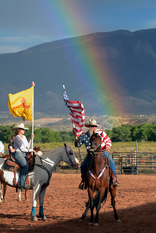 gbs072017i/RIO-WEST  -- Jasmine Rodriguez of Rio Rancho holds the New Mexico flag as Ben Branden of Rio Rancho holds the U.S. flag while calming his horse during the National Anthem at the start of the rodeo at the Stables at Tamaya on Thursday, July 20, 2017.(Greg Sorber/Albuquerque Journal)