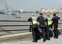 © Licensed to London News Pictures. 25/07/2012. London, UK .  Policemen watch HMS Ocean moored in the Thames for the Olympic games 2012 in the sunshine as temperatures reach 30 degrees at Greenwhich Pier in London today 25 July 2012. Photo credit : Stephen Simpson/LNP