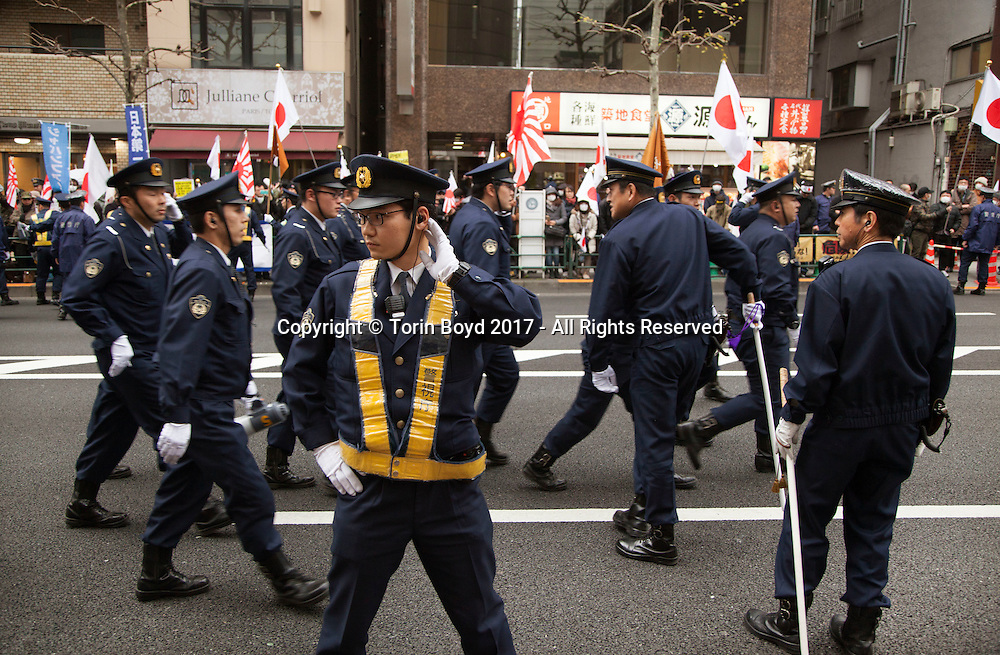 """February 5, 2017, Tokyo, Japan: An angry group of ultra-right wingers demonstrated in front of an APA Hotel branch in Tokyo due to the hotel chain's planned removal of a controversial history revisionist book from rooms hosting athletes of the 2017 Sapporo Asian Winter Games. The book in question written by Toshio Motoya, the hotel chain's Chief Executive, claims the 1937 Nanjing Massacre was a fabrication. Writing under the pen name Seiji Fuji, Motoya's book entitled """"Theoretical Modern History II"""" is placed in every APA Hotel room in Japan and sold at their reception desks. The Tokyo based APA Hotel group is one of the largest hotel chains in Japan with over 400 hotels across the country. In the past 2-3 years APA has benefitted from a tourism boom to Japan in which 40% of their guests are foreign visitors and half that amount are Chinese and Korean nationals. As a result, China and Korea have been outraged by APA and a large boycott began in late January by both countries. This led to APA announcing they would pull Motoya's books from athlete's rooms only during the Asian Winter Games, infuriating Japanese right wingers. The demonstrators at this event are part of a group who call themselves """"Group of Warriors Protecting the Nation"""" (Gokoku Shishi no Kai). Photo by Torin Boyd."""