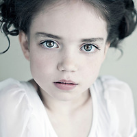 Young girl with hair in plait looking at camera wearing white dress
