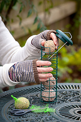 Taking netting off  fat balls and filling a bird feeder