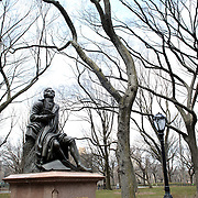 Robbie Burns statue in Central Park, Manhattan, New York. Robert Burns (1759-1796), Scotland's national poet, is most famous for his song Auld Lang Syne, is depicted on a tree stump having just composed to his love, Mary, a poem which is written on a scroll at his feet. Central Park, Manhattan, New York, USA. 28th March 2013. Photo Tim Clayton