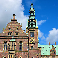 Clock Tower at Frederiksborg Castle in Hiller&oslash;d, Denmark   <br /> This clock tower stands above the chapel wing of the Frederiksborg Castle. It took nine years to build, from 1608 until 1617, as part of the second phase of the slot&rsquo;s construction. The Chapel of Orders is also called the Palace Church.  It was the venue for the coronation of the Danish Absolute Monarchs from 1671 until 1840. This section of the castle is one of the few that survived the 1859 fire.  It is now part of the museum with a display of coats of arms but is also used as a parish church.