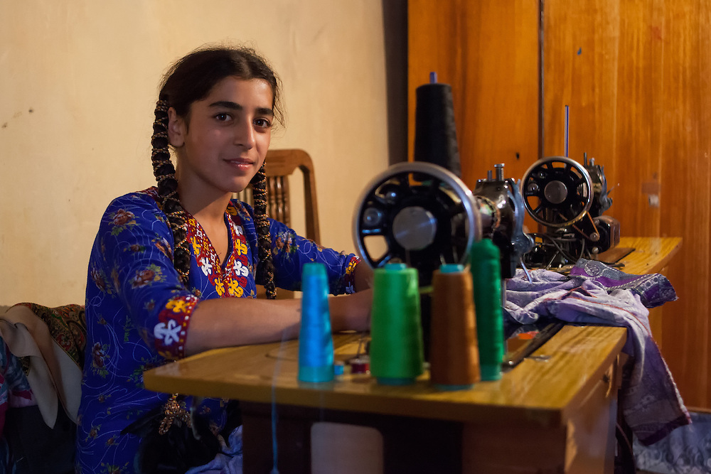 A young Turkmen woman sewing traditional clothing in Nokhur village