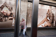A middle-aged woman walks past a large ad billboard for the Body fragrance Burberry Group plc, a British luxury fashion house, manufacturing clothing, fragrance, and fashion accessories. Rosie Alice Huntington-Whiteley (born 18 April 1987) is an English model and actress unveiled as the face of Burberry's newest fragrance, Burberry Body, in July 2011 but also best known for her work for Victoria's Secret, Burberry, and her role as Carly Spencer in the 2011 film Transformers: Dark of the Moon, part of the Transformers film series