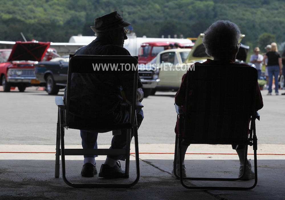 Wurtsboro, NY - An elderly couple sits in the shade during a car show at Wurtsboro Airport on Aug. 30, 2009.