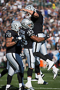 Oakland Raiders tackle Donald Penn (72), running back DeAndre Washington (33) and quarterback Derek Carr (4) celebrate a touchdown against the Tennessee Titans at Oakland Coliseum in Oakland, Calif., on August 26, 2016. (Stan Olszewski/Special to S.F. Examiner)