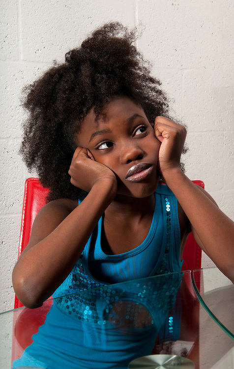 African American girl seated pensive with worried expression.