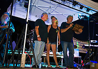 John and Brenda Ganong on stage with Nick Tamposi as awards were given to them and other organizers of the first annual Biketemberfest at Weirs Beach on Saturday evening.  (Karen Bobotas/for the Laconia Daily Sun)