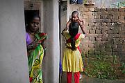 Next to her mother Kitabun Bibi, 45, (left) Tabasum Khatun, 14, is lifting her neighbour's toddler while standing in their courtyard in Algunda village, pop. 1000, Giridih District, rural Jharkhand, India.