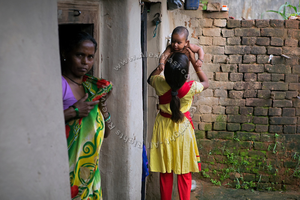 Next to her mother Kitabun Bibi, 45, (left) Tabasum Khatun, 14, is lifting her neighbour's toddler while standing in their courtyard in Algunda village, pop. 1000, Giridih District, rural Jharkhand, India.