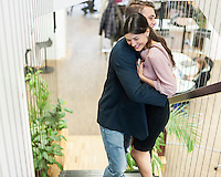 Side view of young business couple hugging on staircase
