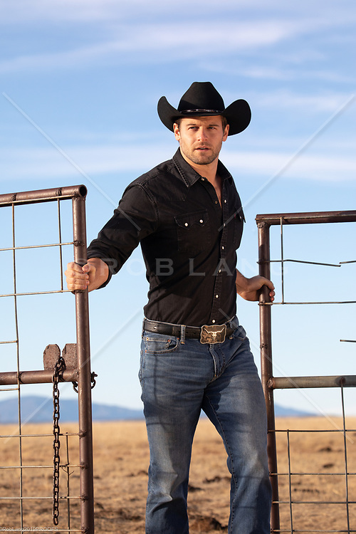 rugged cowboy opening a gate on a ranch