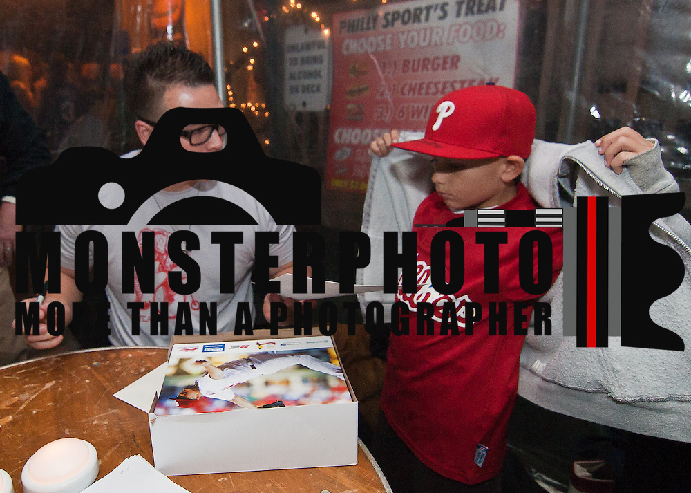 12/14/11 Wilmington DE: Phillies Pitcher Vance Worley (Left) hands Dante Claudio 8 an Autographs photo at 3rd Annual Delaware KIDS Fund Holiday Food Drive Wednesday Dec. 14, 2011 at James Street Tavern in Newport Delaware.<br /> <br /> Special to The News Journal/SAQUAN STIMPSON<br /> <br /> At Holiday Food Drive, everybody pitches in:<br /> http://www.delawareonline.com/article/20111215/NEWS/112150328/At-Holiday-Food-Drive-everybody-pitches-in?odyssey=mod%7Cnewswell%7Ctext%7CHome%7Cs