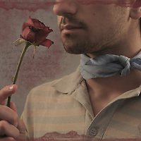 A young man wearing a scarf holding a red rose