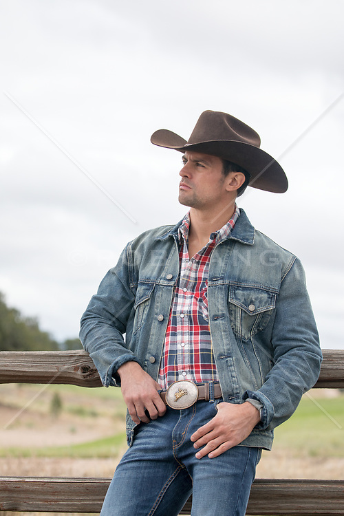 rugged cowboy leaning against a fence