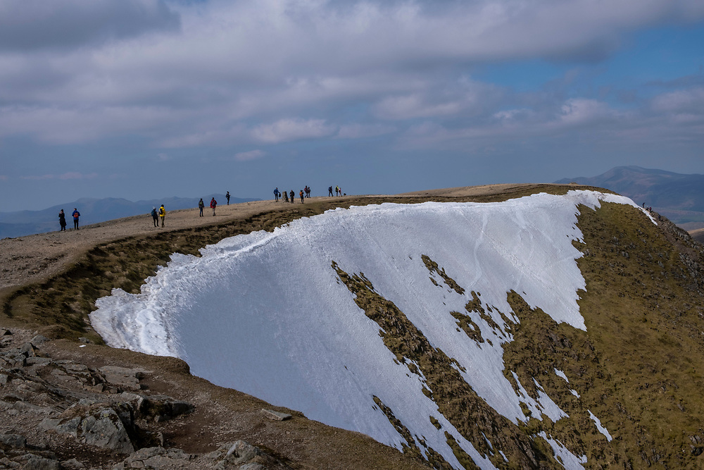 Groups of people walking along the plateau path towards the summit of Helvellyn Mountain, Lake District, Cumbria, UK. It is a bright, sunny day, but there is snow on the mountain side. Helvellyn is the third-highest point in England and is located in the beautiful Lake District National Park and part of the Eastern Fells. (photo by Andrew Aitchison / In pictures via Getty Images)