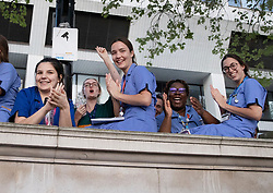 © Licensed to London News Pictures. 23/04/2020. London, UK. Nurses and other medical staff clap and cheer at 8pm for the weekly Clap for Carers celebration outside St Thomas' Hospital in central London. Lockdown continues throughout the UK in an attempt to stop the spread of the coronavirus Covid-19 virus. Photo credit: Peter Macdiarmid/LNP