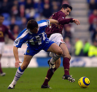 Photo: Jed Wee.<br />Wigan Athletic v Arsenal. The Barclays Premiership.<br />19/11/2005.<br />Wigan's Arrian de Zeeuw (L) tries to dispossess Arsenal's Robin van Persie.