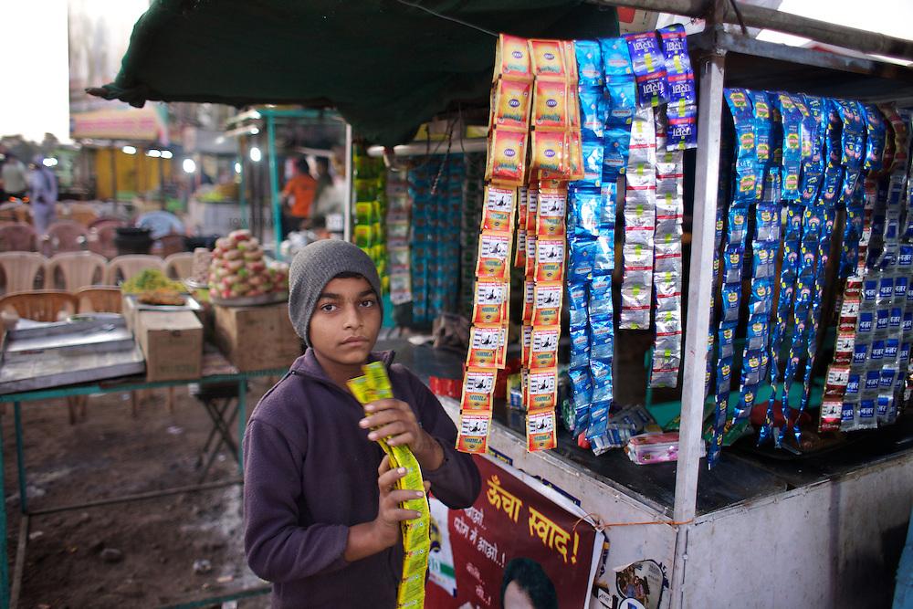 Sonny, age 14, works at a paan (tabacco) stall outside Shegaon's railway station. ..Photo: Tom Pietrasik.January 2011.Maharashtra, India