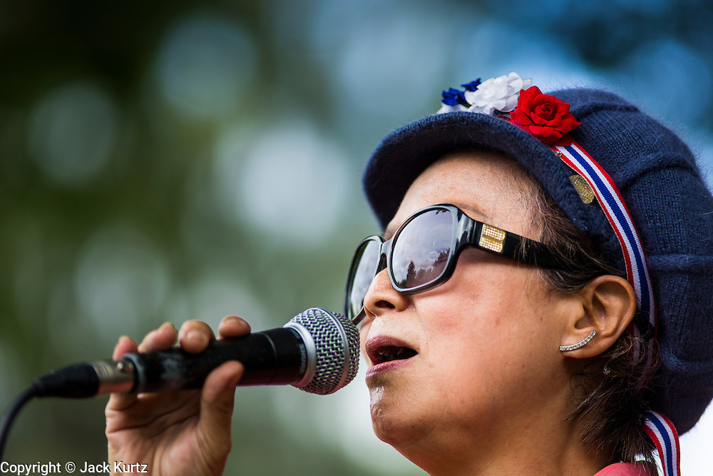 """15 JUNE 2014 - BANGKOK, THAILAND: A woman wearing a Thai patriotic headband sings folk songs on a stage during a """"Return Happiness to Thais"""" party in Lumpini Park in Bangkok. The Thai military junta, formally called the National Council for Peace and Order (NCPO), is sponsoring a series of events throughout Thailand to restore """"Happiness to Thais."""" The events feature live music, dancing girls, military and police choirs, health screenings and free food.    PHOTO BY JACK KURTZ"""