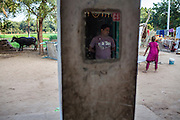 Kantibhai Solanki (center), 38, looks out to their farm and buffalo at their house, built using the money his wife, Sharda made from doing 2 surrogacies, in Anand, Gujarat, India on 9th December 2012. While Kantibhai works as a security guard earning 5000 rupees per month, Sharda, 36, had made hundreds of thousands with 2 surrogacies that she did with Akanksha Clinic, which she used to buy land, buffaloes, build washrooms in her house and extend the house. She had also saved a substantial amount to fund her 3 children's educations and make sure that her 2 daughters will find husbands to match their current status. Photo by Suzanne Lee / Marie-Claire France