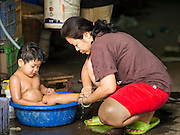 11 JANUARY 2015 - BANGKOK, THAILAND: A woman bathes her son in a blue plastic tub in Pak Khlong Talat, the flower market in Bangkok. The market, which runs along the Chao Phraya River, is the largest flower market in Thailand.     PHOTO BY JACK KURTZ