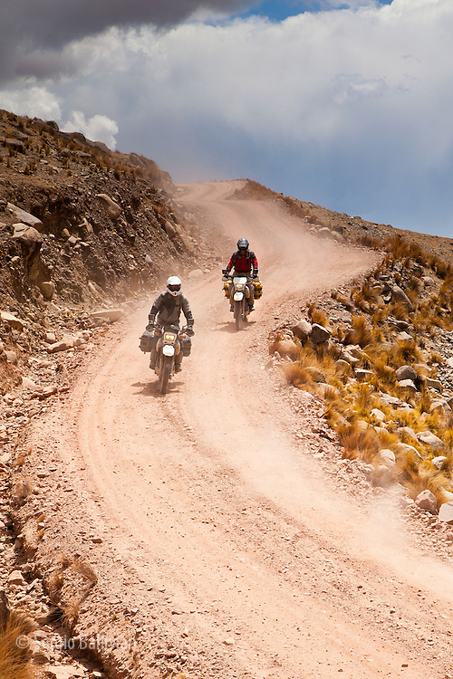 Motorcyclists navigate a narrow mountain road in the Cordillera Quimsa Cruz, Bolivia.