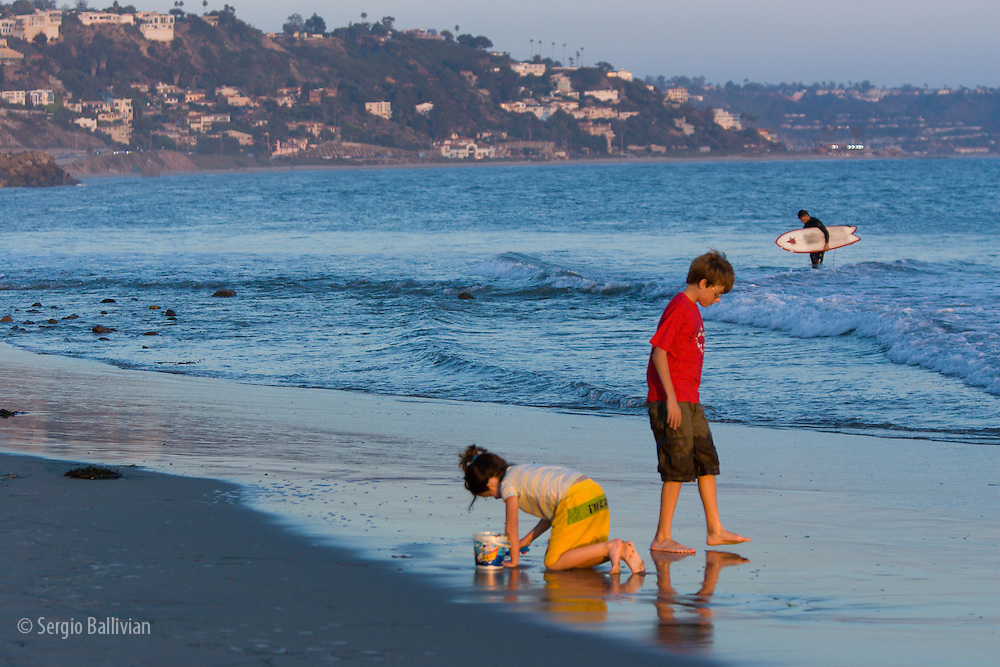 Kids are playing on the beach in Malibu, California