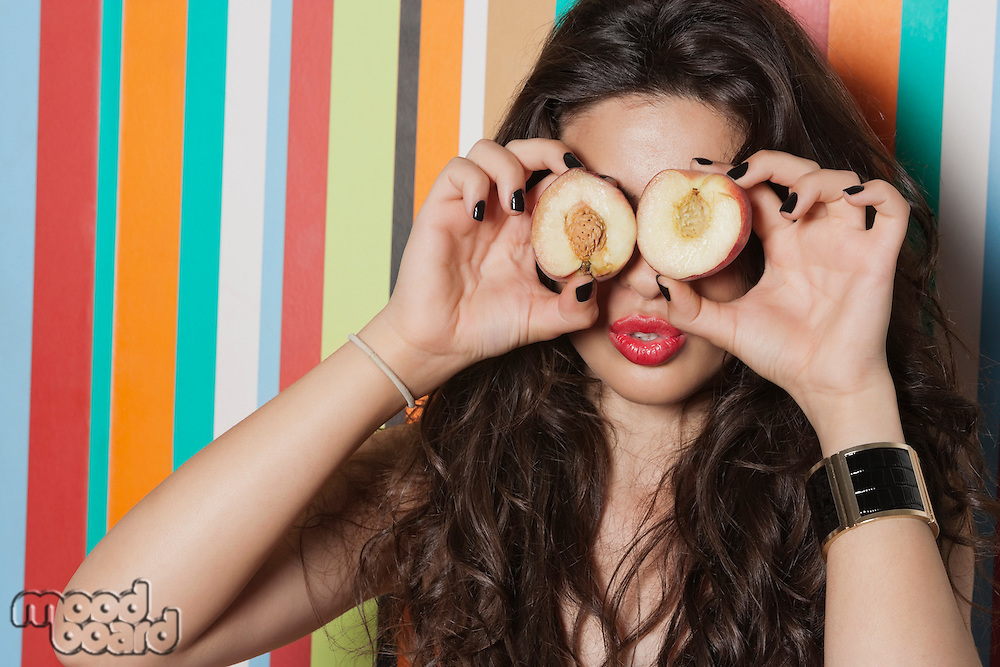 Young woman covering her eyes with peach against striped background