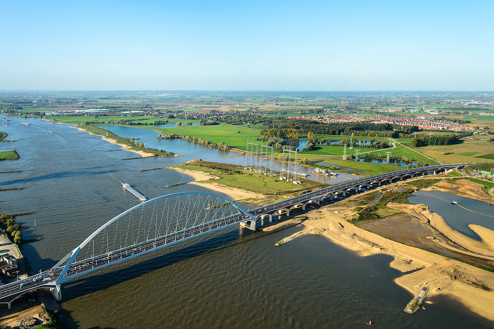 Nederland, Gelderland, Nijmegen, 24-10-2013; de nieuwe stadsbrug van Nijmegen over rivier de Waal, De Oversteek. Aan de andere kant van de rivier grondwerkzaamheden voor de Dijkteruglegging Lent (Ruimte voor de Rivier) en Nijmegen-Noord. <br /> The new city bridge of Nijmegen on the river Waal, De Oversteek (The Crossing). On the other bank of the river groundwork for the Dike relocation of Lent (project Ruimte voor de Rivier: Room for the River). <br /> luchtfoto (toeslag op standaard tarieven);<br /> aerial photo (additional fee required);<br /> copyright foto/photo Siebe Swart.
